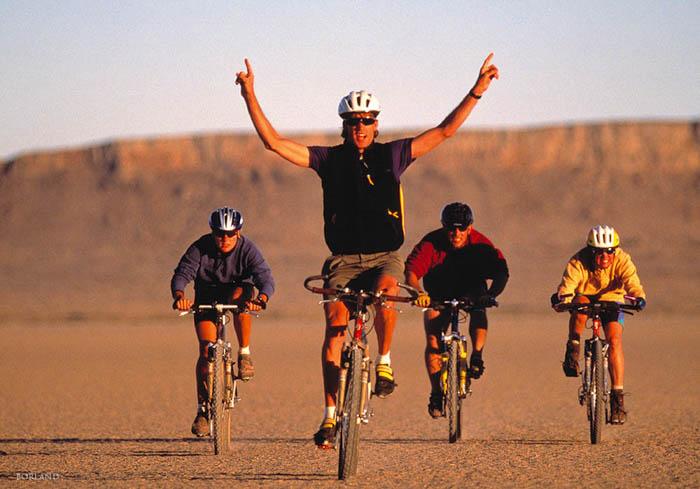 quatro homens em bicicletas em um deserto