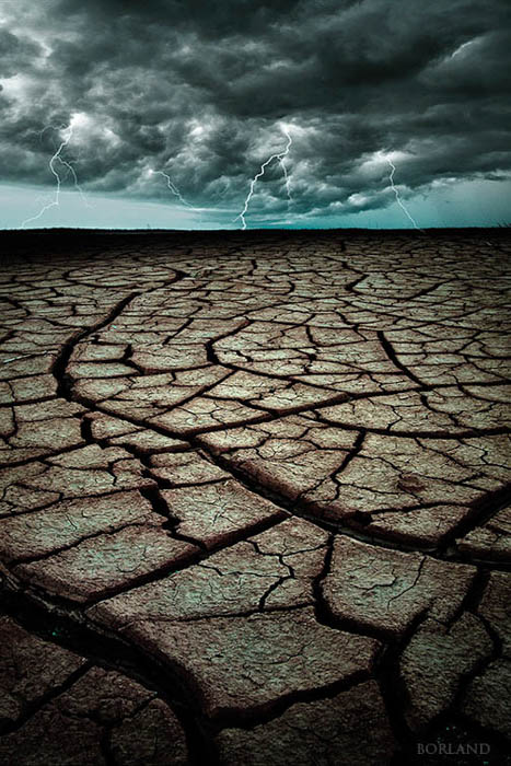 Death Valley cracked sand photo with lightning storm composited in Photoshop in the background