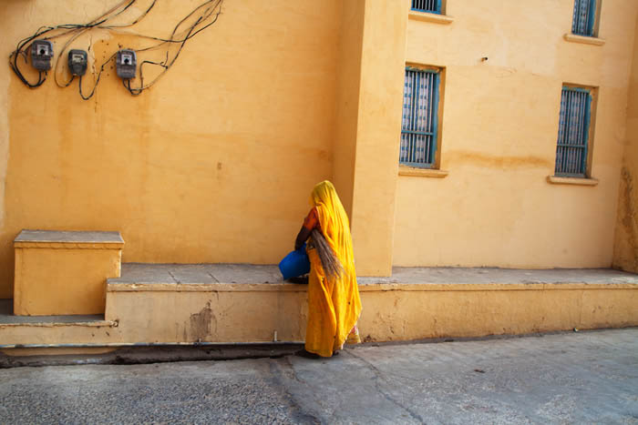 using colour in photography composition, picture shows a woman dressed in yellow with her back to the camera, facing the yellow wall of a building