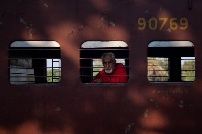 picture of a man looking out the window of a train compartment