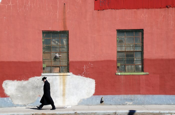 A man in a suit and hat walks past a red wall