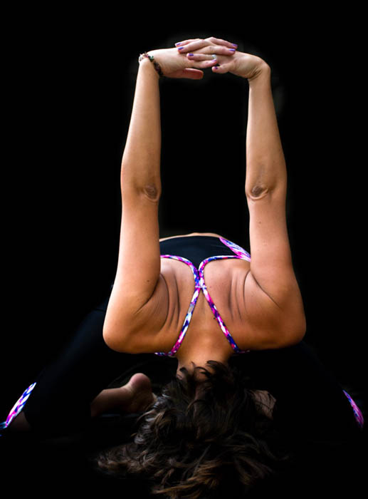 Photo of a yogini in a forward bend pose, showing creative use of black background in photography