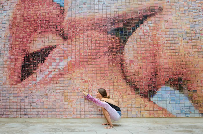 Artistic yoga photography of a model in firefly pose in front of a mosaic wall showing two people kissing
