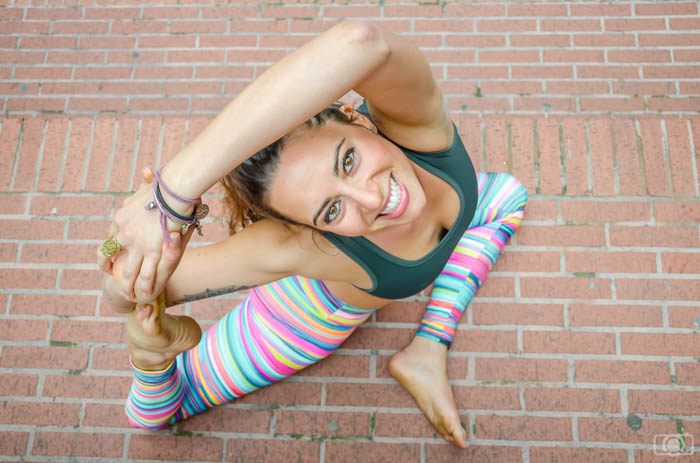 high angle photo of a yoga model wearing bright leggings and smiling up at the camera