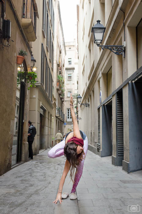 photo of a woman in a variation of the yoga tree pose, photographed on a narrow empty street