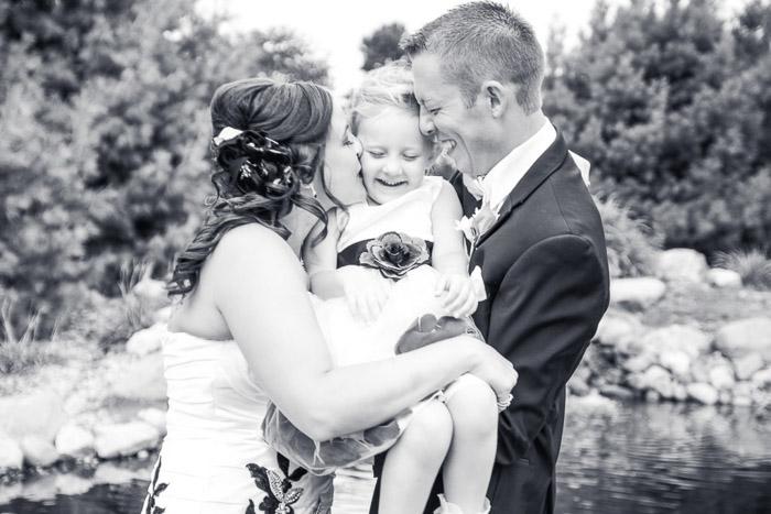 Foto em preto e branco do casamento de um casal segurando uma garota