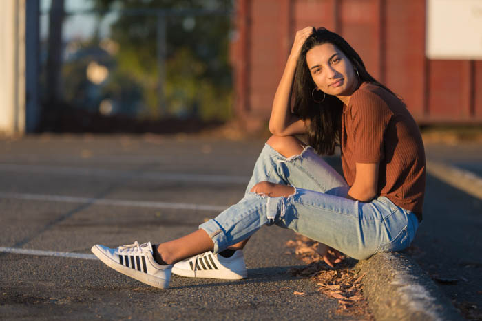 A girl posing sitting on the ground of an outdoor carpark