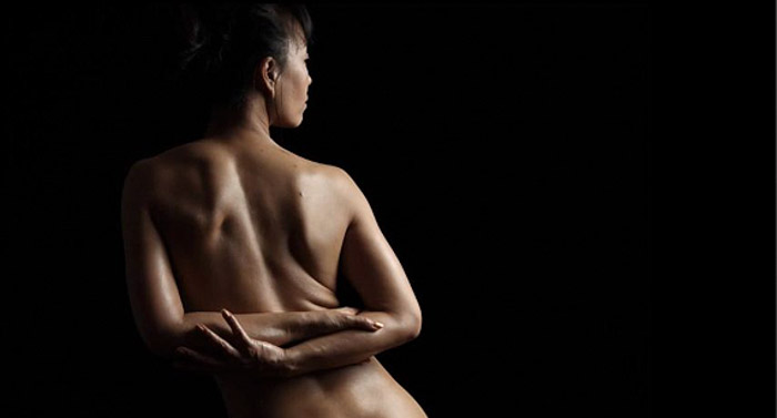 A woman's back, showing one light is a great way to take stunning boudoir photography