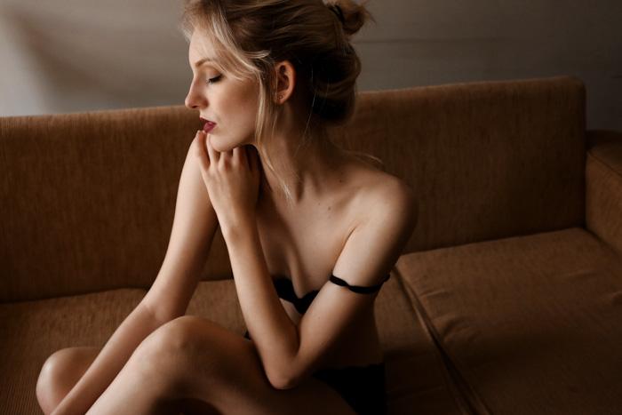 Foto de boudoir de uma mulher loira sentada em um sofá