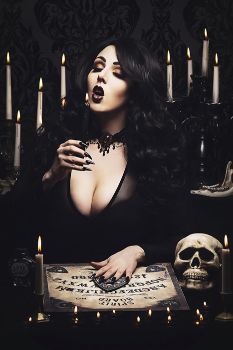 Gothic style portrait photo of a woman blowing out a candle