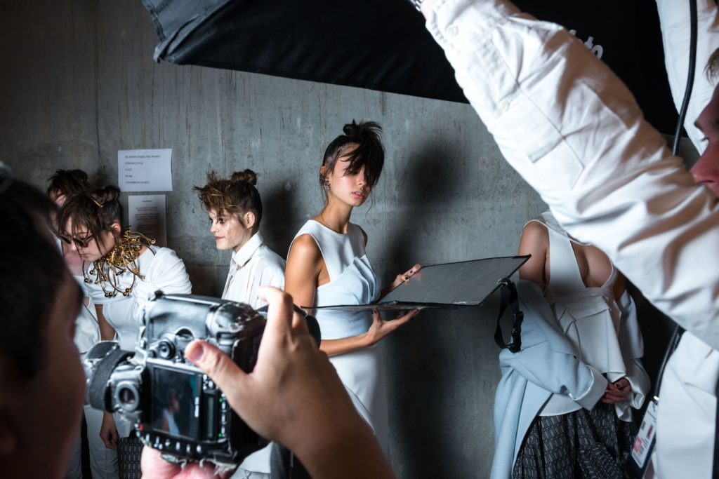 An image showing the behind the scenes of a fashion photography shoot