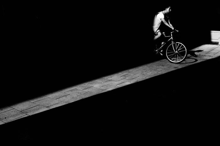 Showing the use of strong shadows with an image of a cyclist entering a slice of light