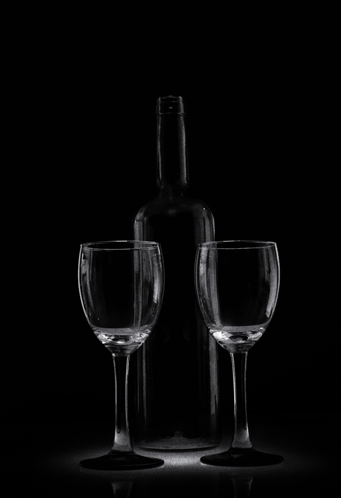 Dois copos e uma garrafa de vidro ficam em um ambiente escuro e discreto