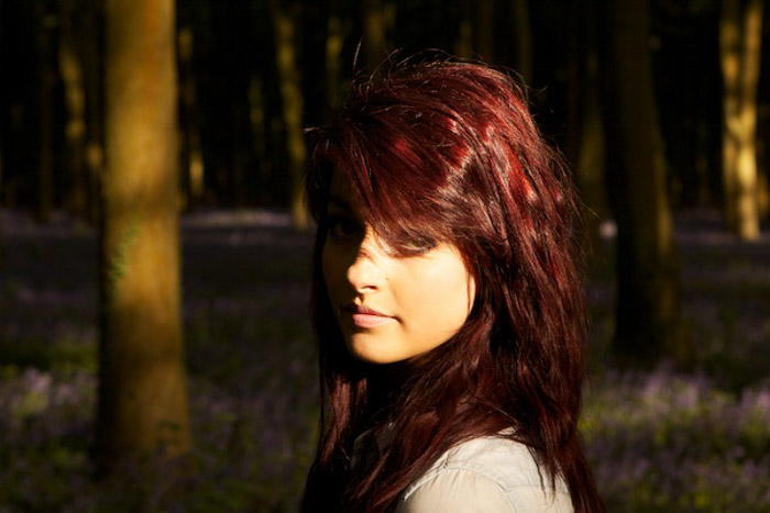 A portrait of a female model in a forest shot with partial metering mode