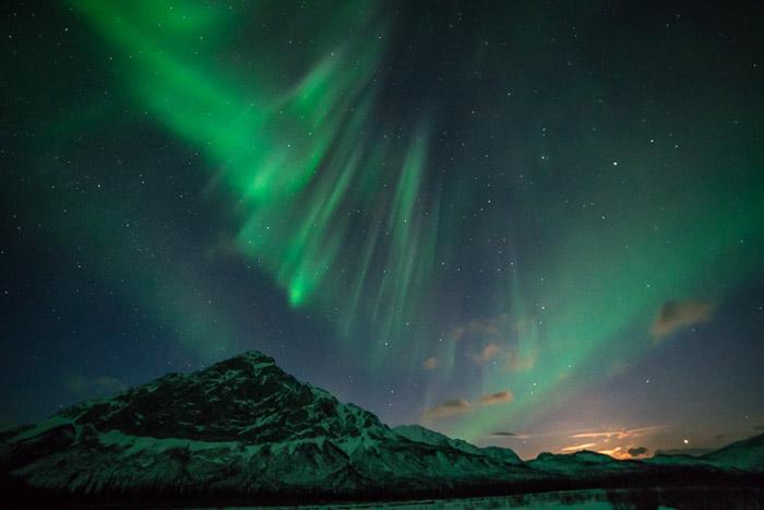 A aurora boreal em uma paisagem montanhosa