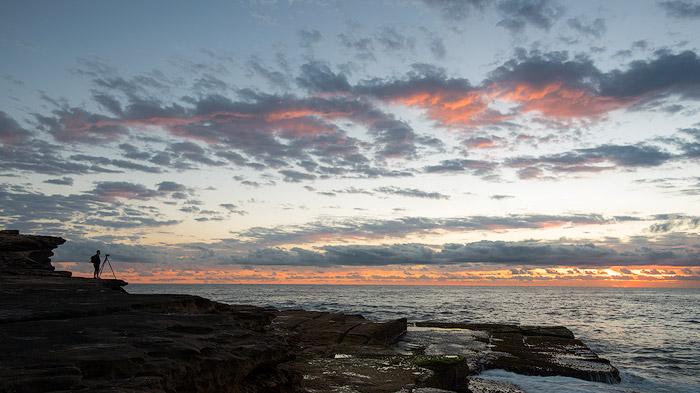 A photographer taking sunrise photography at a rocky coast