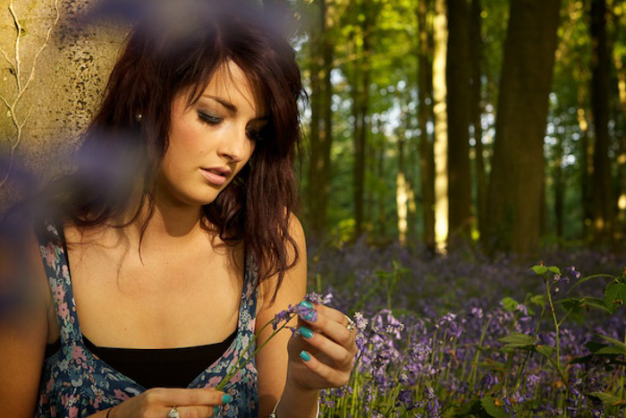 An outdoor portrait of a female model holding purple flowers