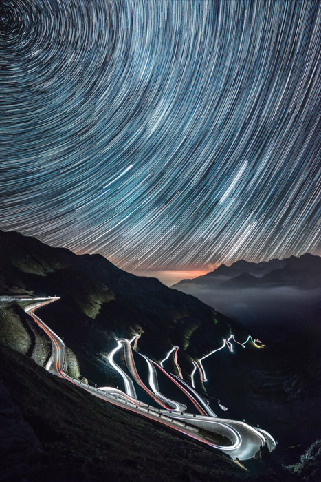 Star trails photographed over a windy road adds two levels of time-lapse photography