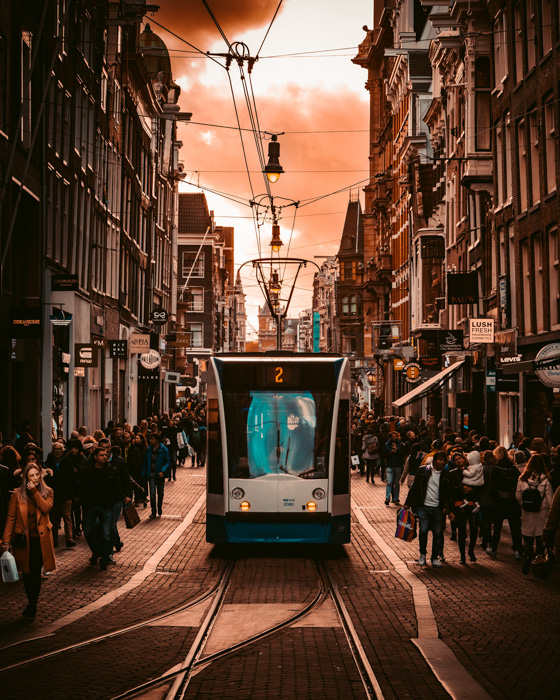 An orange and cyan toned street photography shot with a tram and crowds