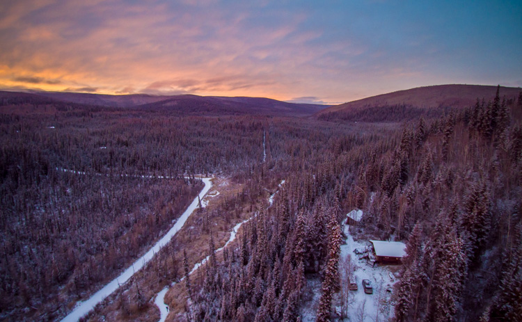 Aerial photography view of a forest, houses and mountains taken by a drone at sunset