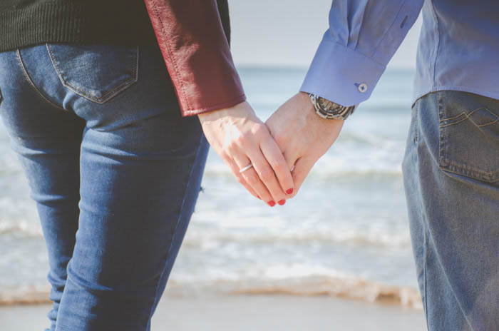 a close up of a couple posing and holding hands on the beach
