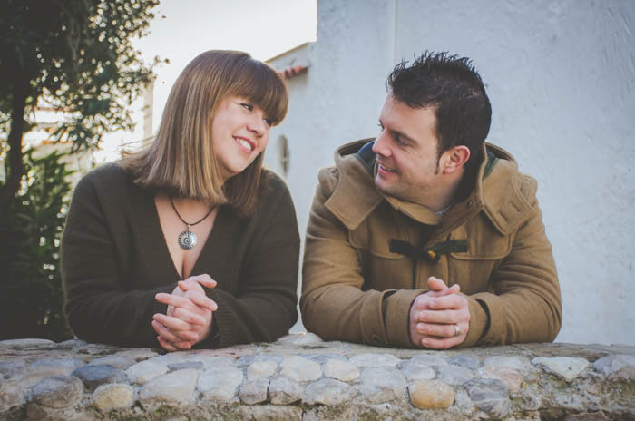 a couples photography portrait - leaning on a stone fence and smiling