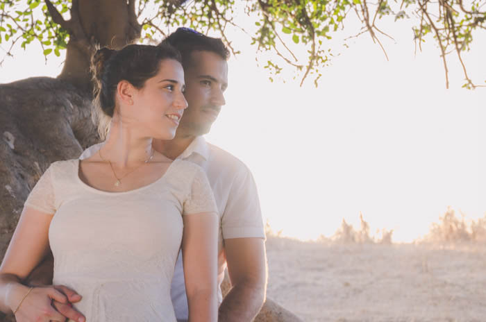 a portrait of a couple pose outdoors