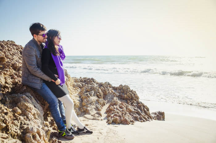 A couple posing on the rocks of a beach
