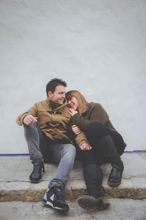 Relaxed photo of a couple sitting on the grounds smiling and holding each other