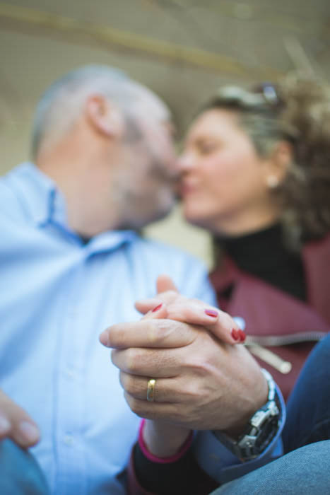 A creatively blurry close up of a couple kissing and holding hands - couple photography tips