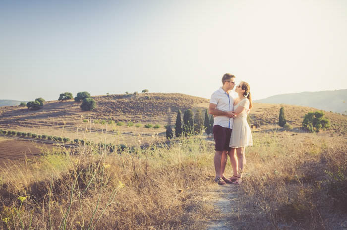 A couple pose embracing in a sunny landscape