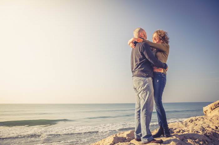 A couples photography pose embracing on a beach
