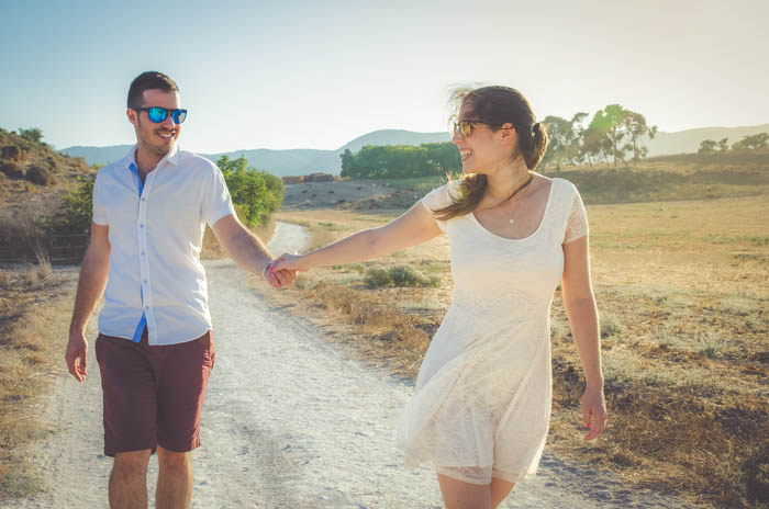 a couple pose holding hands and walking down a countryside path