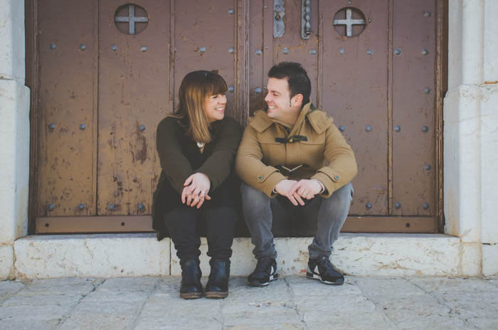 A couple sitting on stone steps and smiling at each other