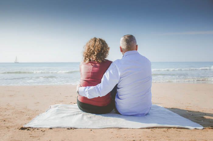 A couple pose sitting on the beach