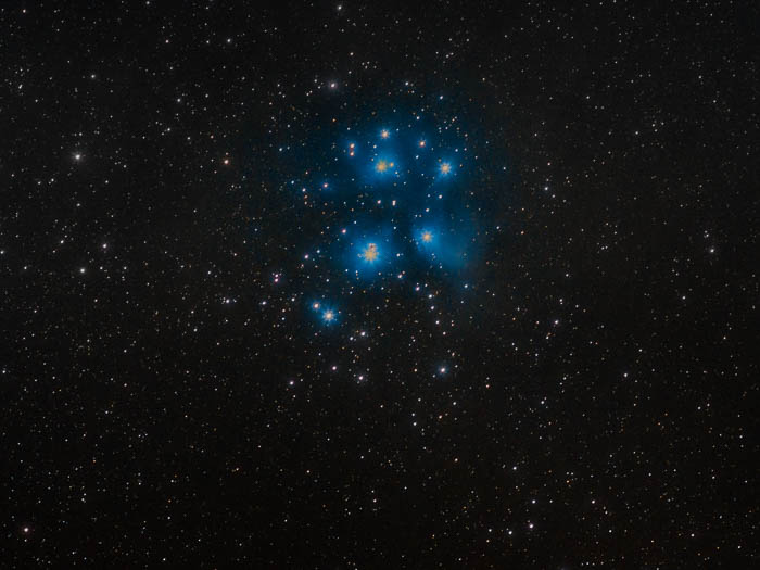 A night sky photography shot of Pleiades and their classic blue nebulosity