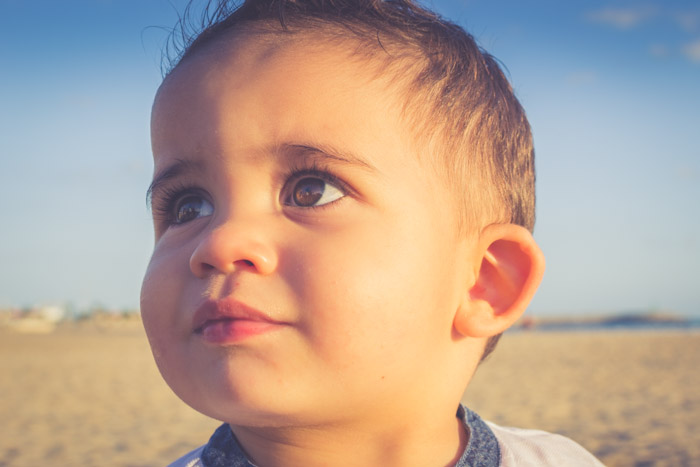 A boy looks off camera in a beach location during the golden hour