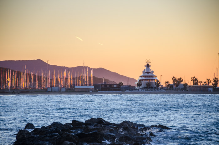 A yacht next to a marina during the golden hour