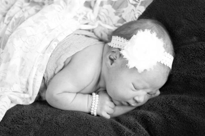 traditional newborn photo of sleeping baby on blankets with headband and pearl bracelet