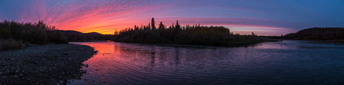 Atmospherica and brightly coloured panoramic photo of a sunset in Anvik, Alaska