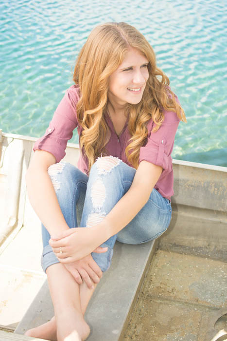 portrait of a redheaded girl sitting on a pier with light reflectors used for lighting