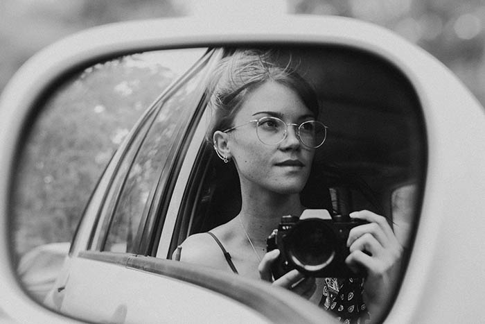 creative black and white self portrait of a young woman in the mirror of her car