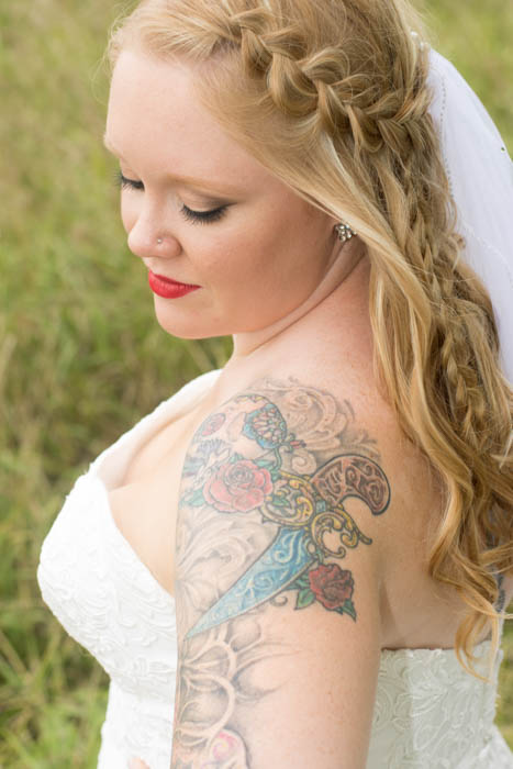 A portrait of a tattooed bride posing outdoors