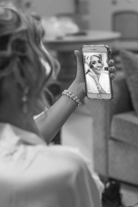 A black and white wedding photo of bride taking a selfie while doing makeup