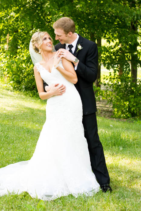 A wedding portrait of bride and groom posing together and laughing, leaning to the right