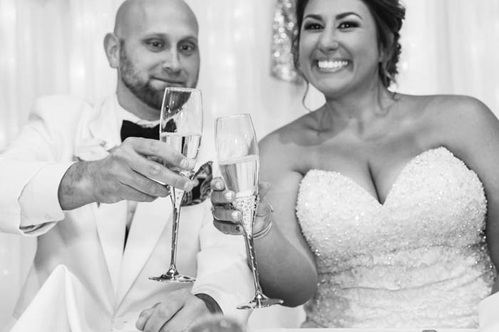 A black and white portrait of a bride and groom toasting at their wedding reception