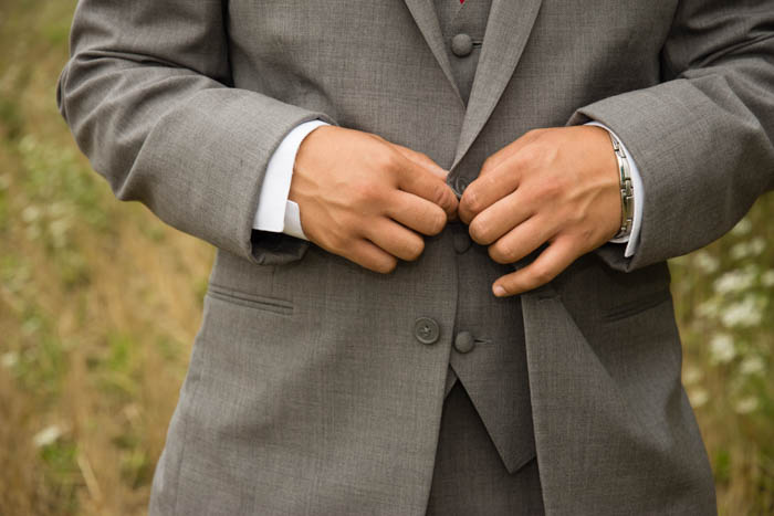 A Wedding portrait close up of a groomsman buttoning his jacket