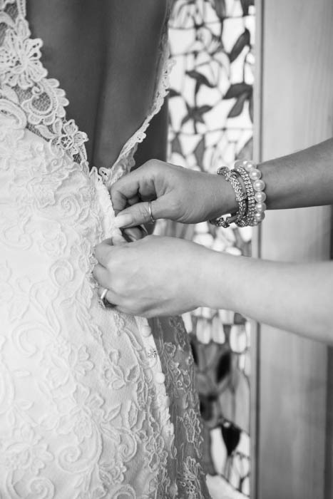A black and white wedding photo of mother of the bride buttoning wedding dress