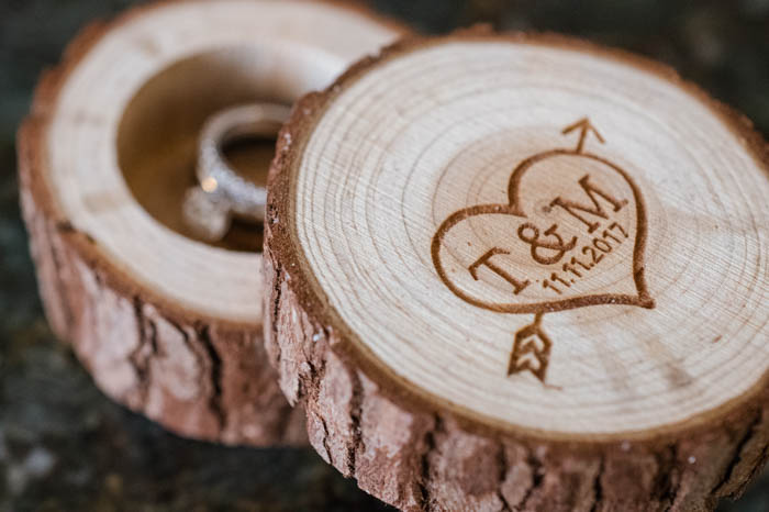 An engagement ring box made out of wood with a heart and arrow with the bride and groom's initials