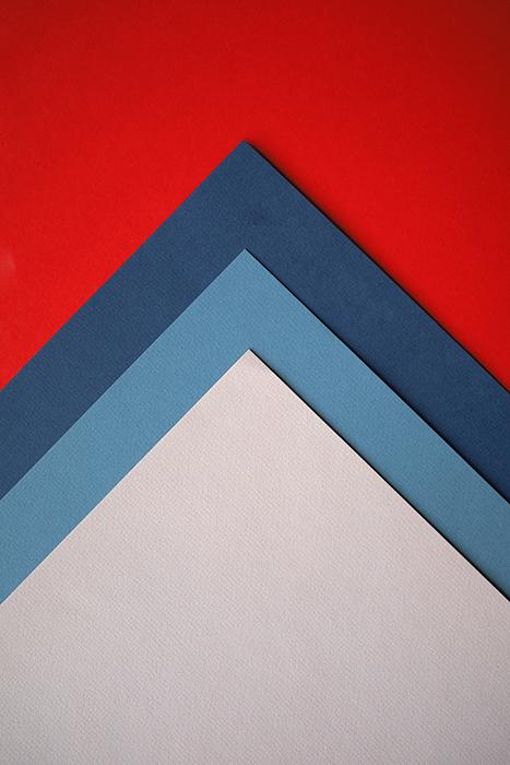 Uma composição abstrata de papel colorido vermelho, azul e cinza